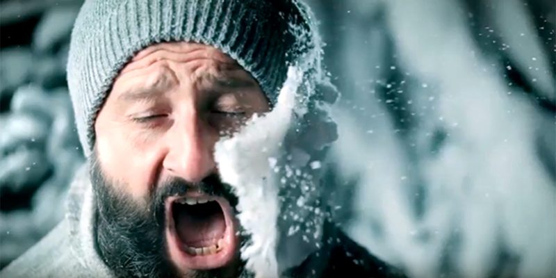 A picture of a man getting hit in the side of the face with a snowball.